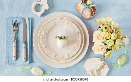 Easter place setting with easter bunny egg on a plate on blue colors. Toned photo.