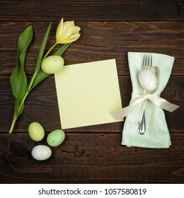Easter Place Setting with invite card, eggs, and daffodil done in light green and yellow tones, on dark rustic wood board background with room or space for copy, text or your word.  Square flat layout