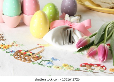 Easter place setting on an elegant linen table cloth.  This traditional holiday brunch place setting includes painted eggs, an embroidered Easter basket and pink tulips.