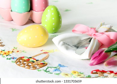 Easter place setting on an elegant linen table cloth.  This traditional holiday brunch place setting includes painted eggs, an embroidered Easter basket, and springtime pink tulips.