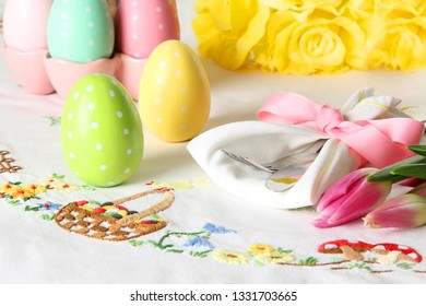 Easter place setting on an elegant linen table cloth.  This holiday brunch place setting includes painted eggs, an embroidered Easter basket, and springtime pink tulips.