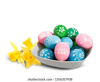 Easter plate with Easter eggs and daffodils isolated on a white background