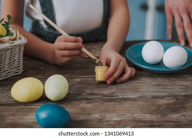 Easter preparing masterclass. Close up cropped head portrait of little female child holding brush to coloring eggs in yellow on wooden table