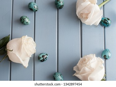 Easter quail eggs with roses on blue background top view