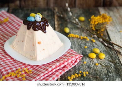 Easter Quark Dessert with Orange Jam, Traditional cottage cheese dessert Paskha decorated with chocolate and candy eggs on wooden background with a red and white checkered napkin