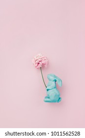 Easter rabbit figurine with a pink flower, on pink background. Ceative flatlay with plenty of copy space for text, minimal composition