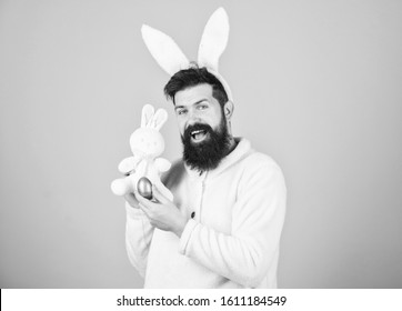 Easter rabbit. Man wearing rabbit suit play with toy. Funny bunny man soft ears. Easter activities concept. Still childish. Celebrate Easter. Guy bearded hipster cheerful bunny with long white ears.