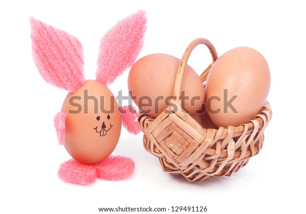 Easter rabbit out of the eggshell and a basket with chicken eggs isolated on white background