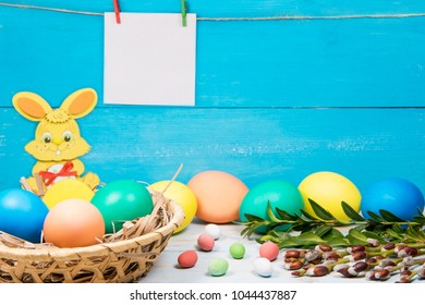 Easter rabit and eggs in a Basket, painted in different color on a blue background with a place for the inscription and green twig