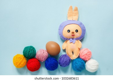 Easter rubbit toy with egg and multi-colored ball on the blue backgraund