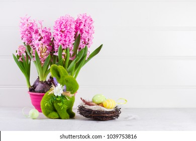 Easter scene with spring flowers, rabbit and nest of eggs