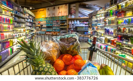 Easter shopping Grocery cart at a colorful supermarket filled up with food products as seen from the customers point of view
