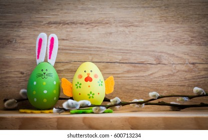 easter spring card - colored bunny and chicken painted eggs on wooden backgound