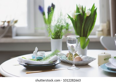 easter and spring festive table decorated in blue and white tones in natural rustic style, with eggs, bunny, fresh flowers and candles.