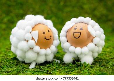 Easter or spring greeting card with two sheep shaped eggs on green background