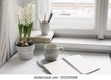 Easter spring still life. Cup of coffee, book and blank open diary mockup near window sill. White hyacinth in flower pot. Pencils in ceramic holder. Home office concept. Scandinavian interior