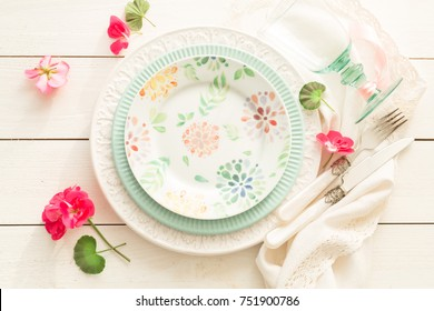 Easter, spring or summer table setting design captured from above (top view, flat lay). Ornamental plates, glass, cutlery and flowers. White wooden background. Outdoor garden party or picnic concept.