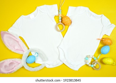 Easter Springtime baby apparel flatlay on bright yellow table with colorful accessories. Twins two baby bodysuit, romper, onesie mock up with negative copy space for your text or design here.
