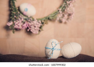 Easter still life background with Easter eggs and flower wreath, pastel colours decoration from rope, ribbon with wooden background