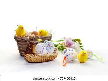 Easter still life. Church candles, eggs in a nest and chick figurines close-up on a table.