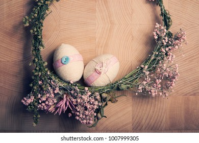 Easter Still life closeup with decorative eggs in pastel pink colours, rope, ribbon and button on flower wreath on the wooden background