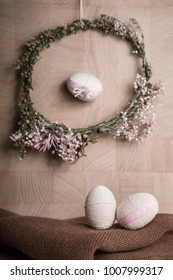 Easter Still life with decorative eggs in pastel colours, rope, ribbon and button with flower wreath on the wooden background