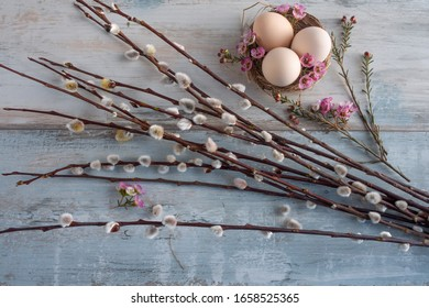Easter still life on vintage background with floral decoration. Natural colored easter eggs in a nest on gray shabby wooden planks. Flat lay photography with space for text. Top view.
