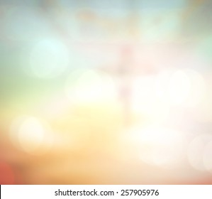 Easter Sunday concept: Blurred Jesus on the cross with crown of thorns over bokeh autumn sunrise background