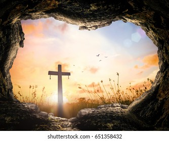 Easter Sunday concept: Empty tomb stone with cross on meadow sunrise background