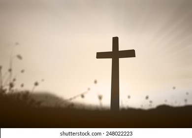 Easter Sunday concept: Silhouette the cross over blurred autumn sunset background