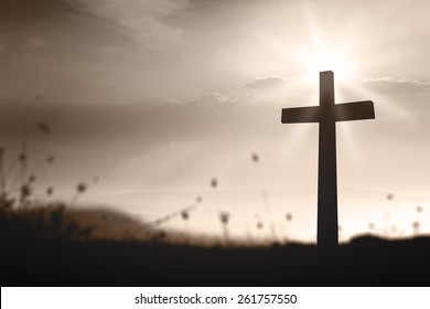 Easter Sunday concept: Silhouette the cross over blurred sunset background