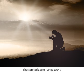 Easter Sunday concept: Silhouette humble christian prayer kneeling and raising hands on sunset background