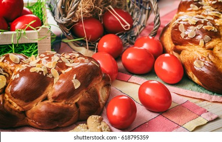 Easter sweet traditional bread, greek tsoureki and red eggs on a table