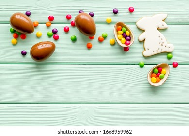 Easter sweets frame. Chocolate eggs and bunny gingerbread on green wooden background top-down frame copy space