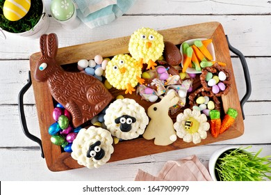 Easter sweets tray with an assortment of desserts and candy. Top view over a white wood background. Spring holiday food concept.