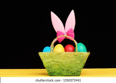Easter symbols concept. Fluffy rabbit ears with colorful eggs in green cloth basket. Bunny ears head band in pink color in basket on black background. Easter decor on yellow wooden table