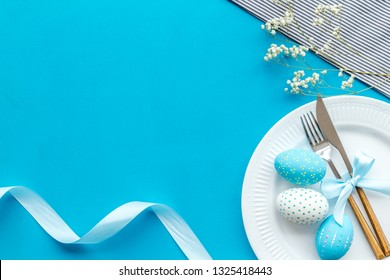 Easter table decoration in blue colors. Plate, cutlery, painted eggs and dry white flowers, tablecloth on blue background top view copy space
