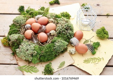 Easter table decoration with moss wreath, hay and eggs.
