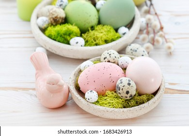 Easter table decorations with eggs, moss and ceramic figurines.