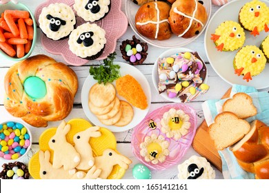 Easter table scene with a selection of breads, desserts and treats. Above view over a white wood background. Spring holiday food concept.
