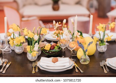 Easter table set in yellow green colors and eggs in the middle