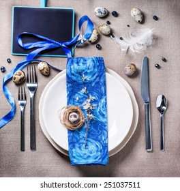 Easter table setting with blue textile napkin, blossom branch and quail eggs. Top view.