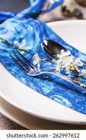 Easter table setting with blue textile napkin and blossom cherry branch
