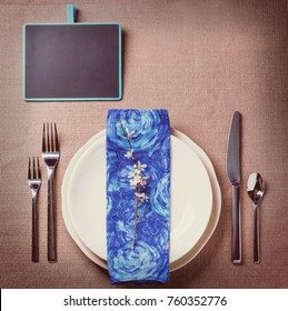 Easter table setting with blue textile napkin, blossom branch and quail eggs. In retro filter effect. Top view.