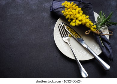 Easter table setting with bright mimosa flowers on dark wooden table with copy space