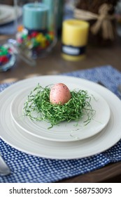 Easter table setting with a decorative spotted pink egg in a crafty diy nest of green Easter grass, candles, and jelly bean candy