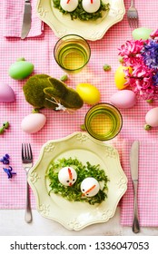 Easter table setting. Funny chickens from eggs served on the Easter table, top view