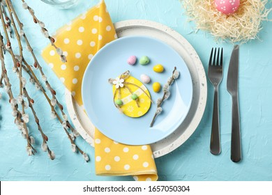 Easter table setting on blue background, top view