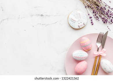 Easter table setting. Tableware and painted eggs on white background top view space for text