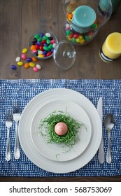 Easter table setting view from above with a decorative spotted pink egg in a crafty diy nest of green Easter grass, candles, and jelly bean candy